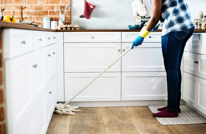 Woman from cleaning services company mops kitchen floor.