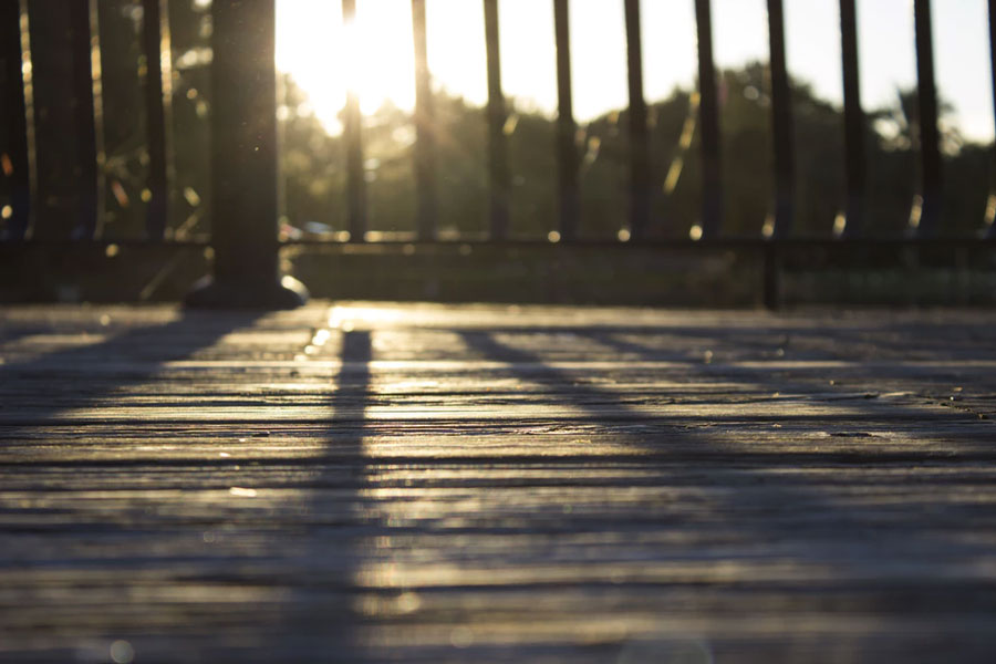 Restored wooden deck boards with the sun shining low through an iron fence.