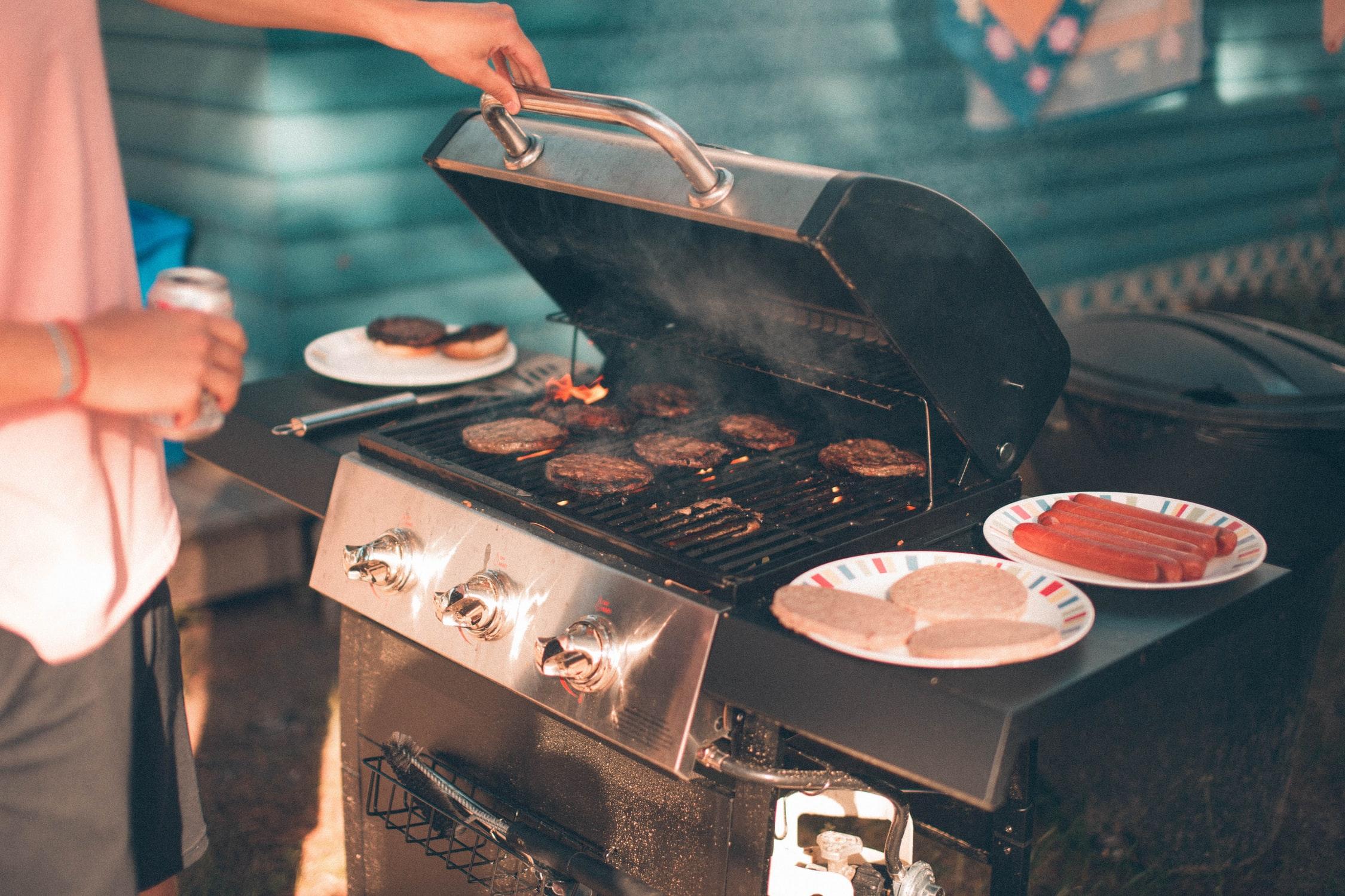 Man lifts BBQ grill lid.