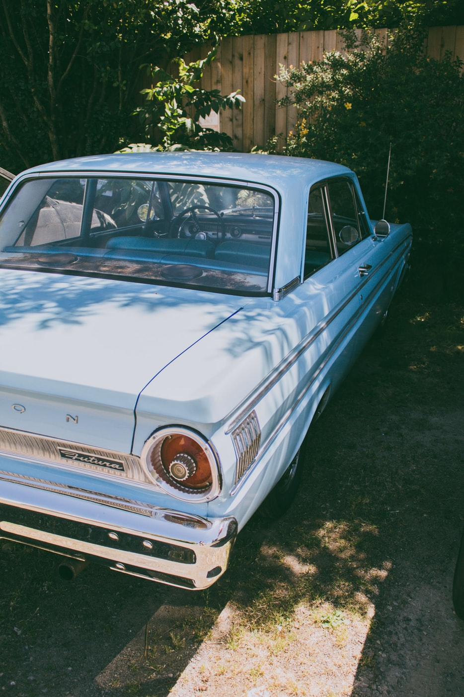 An old blue car parked on a driveway.