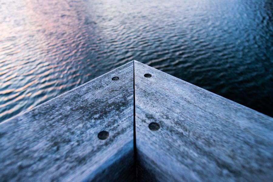 Corner of a restored wooden deck overlooking the water.