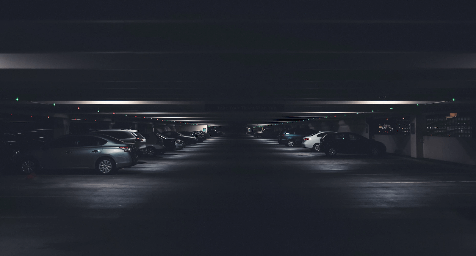 A dark parking garage with lights illuminating the parked cars