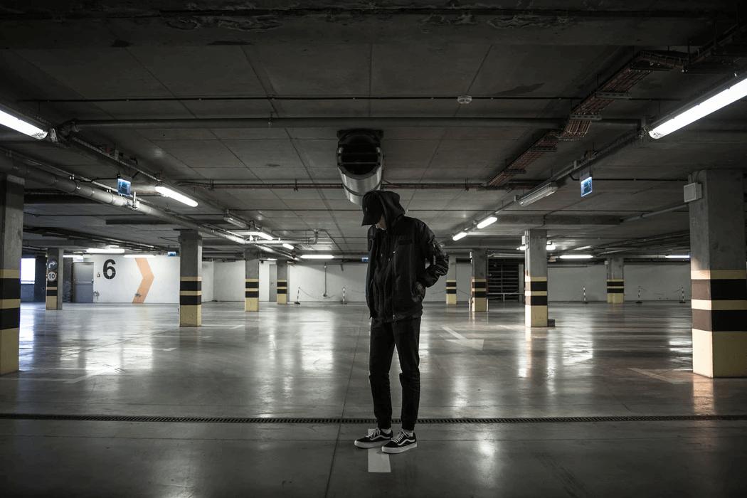 A man standing in an empty parking garage